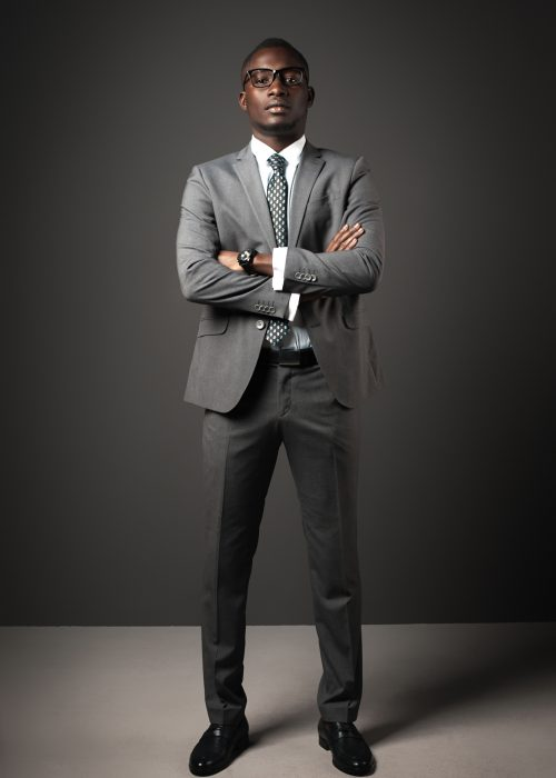 Serious young black man with glasses and gray business suit crossed his arms. Emotional business portrait