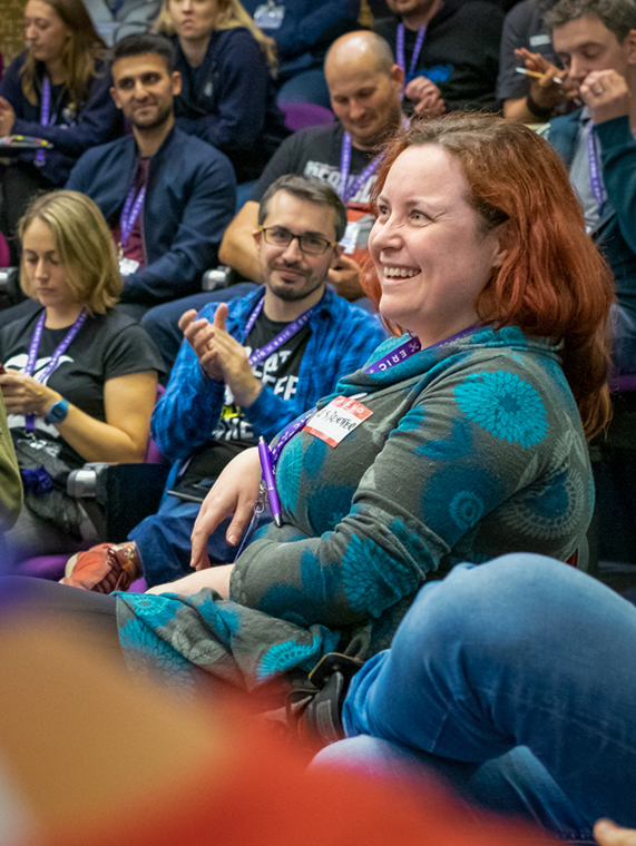 A smiling woman in the audience being applauded