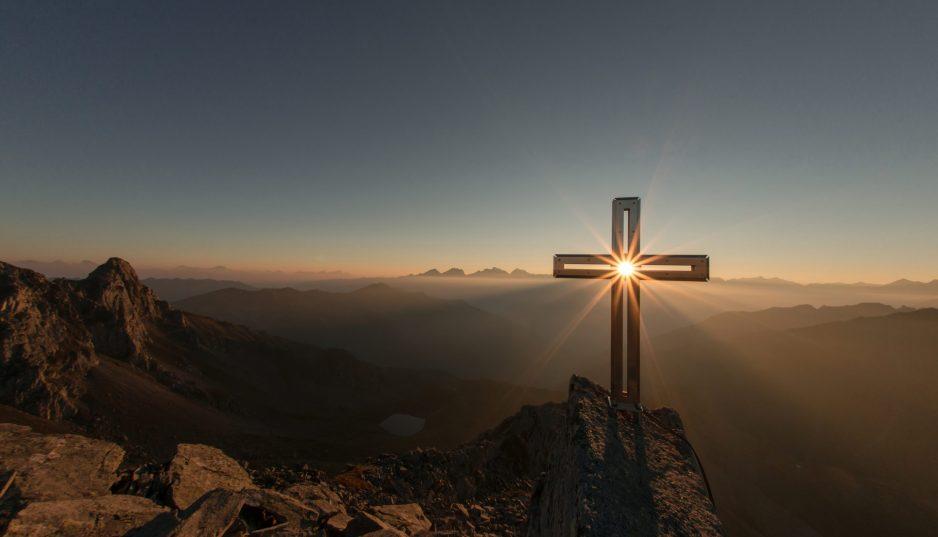 Kors på ett berg. Solens strålar lyser genom korset mot kameran.