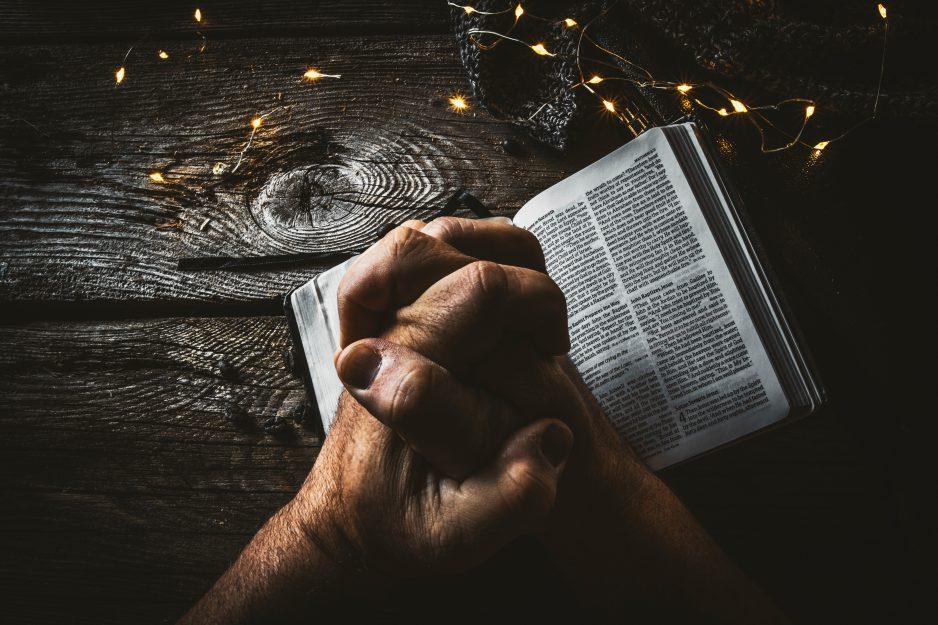 Händer knutna i bön, ligger ovanpå en öppen bibel.