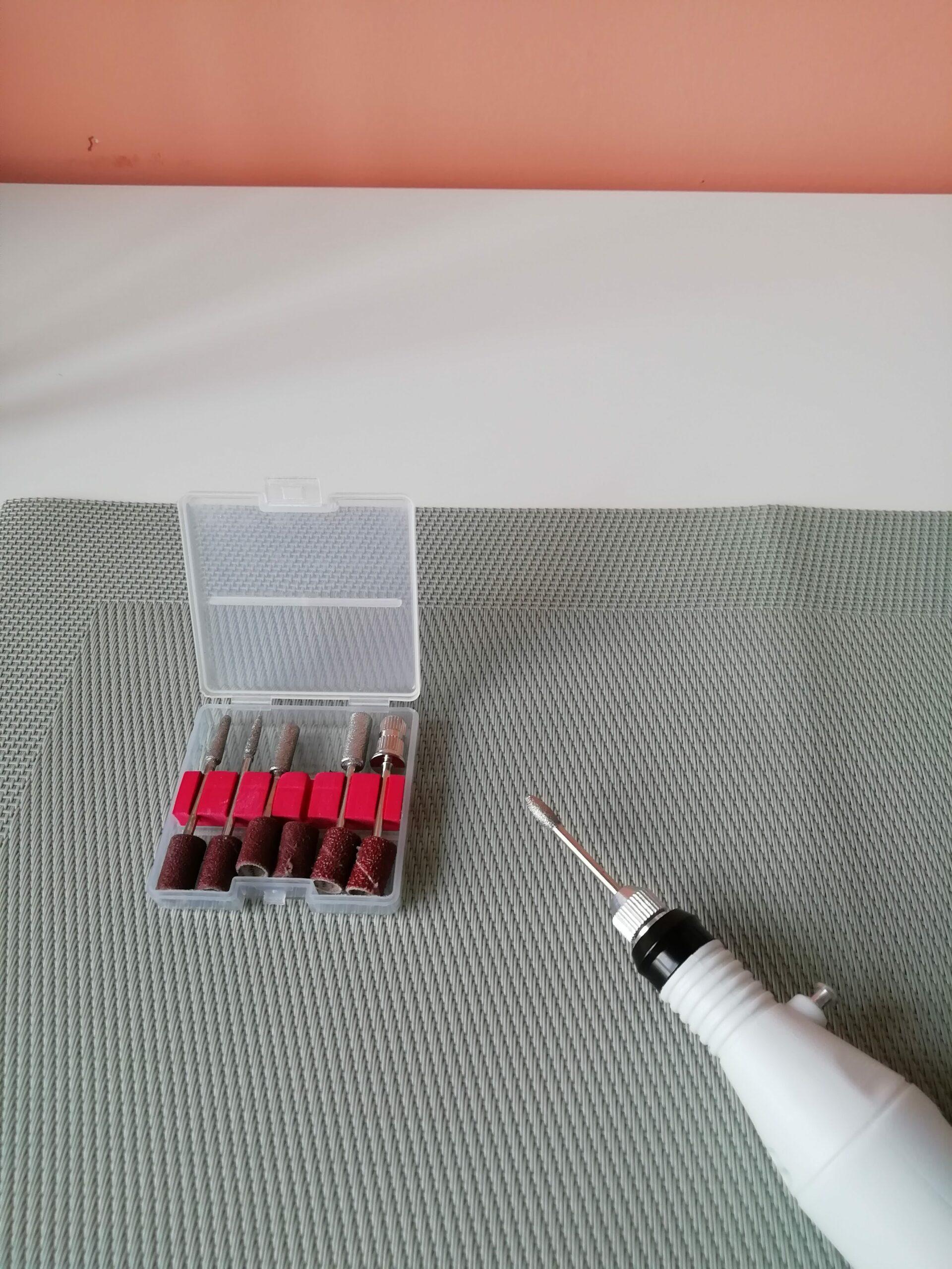 Witte elektrische nagelvijl op groene placemat met roze achtergrond