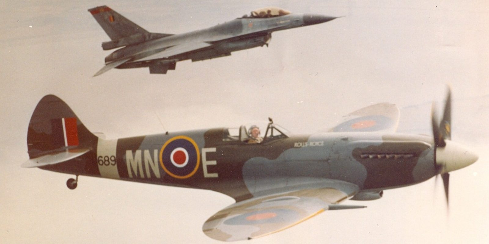Le Spitfire MN-E/RM689 était l'un des rares de son espèce à encore voler le 19 juin 1991, alors qu'il participait au meeting aérien de la base de Beauvechain. Ce Spitfire appartenait au motoriste Rolls-Royce et vole en formation avec un F-16A de la 350. Cet appareil avait fait partie des effectifs de la 350 pour un petit mois en mai 1945. Racheté par Rolls-Royce en 1949, il reçut l'immatriculation civile G-ALGT. Il s'écrasa malheureusement au sol en sortant d'un looping à basse altitude, entraînant le décès de son pilote David Moore le 27 juin 1992 à Woodford. (Archive Squadron 350)