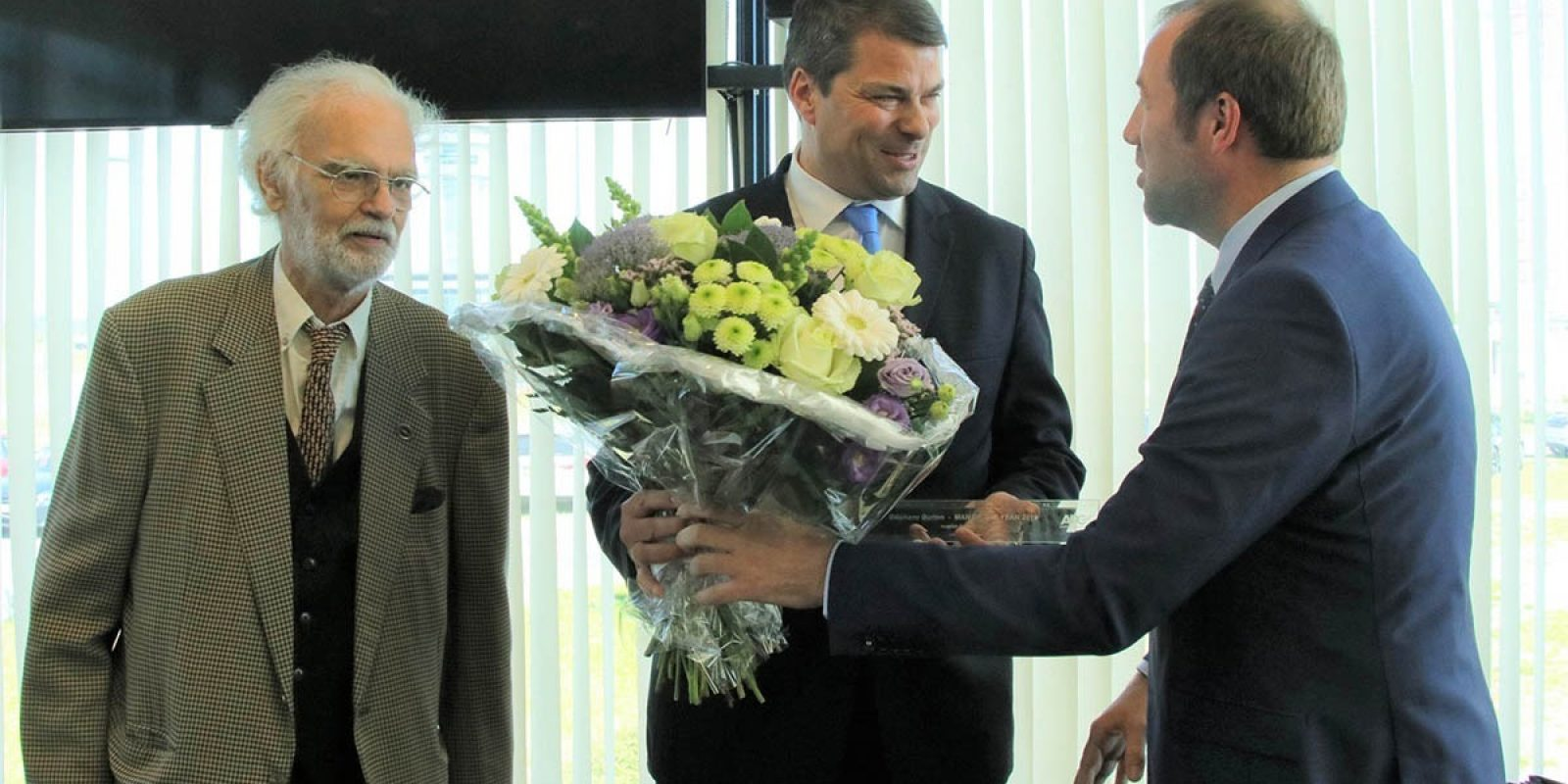 Le nouveau président de l'APC, Steven De Craene, assisté  du président d'honneur Patrick Anspach, remet le trophée MOTY à Stéphane Burton, CEO de Sabena Aerospace. (photo APC)