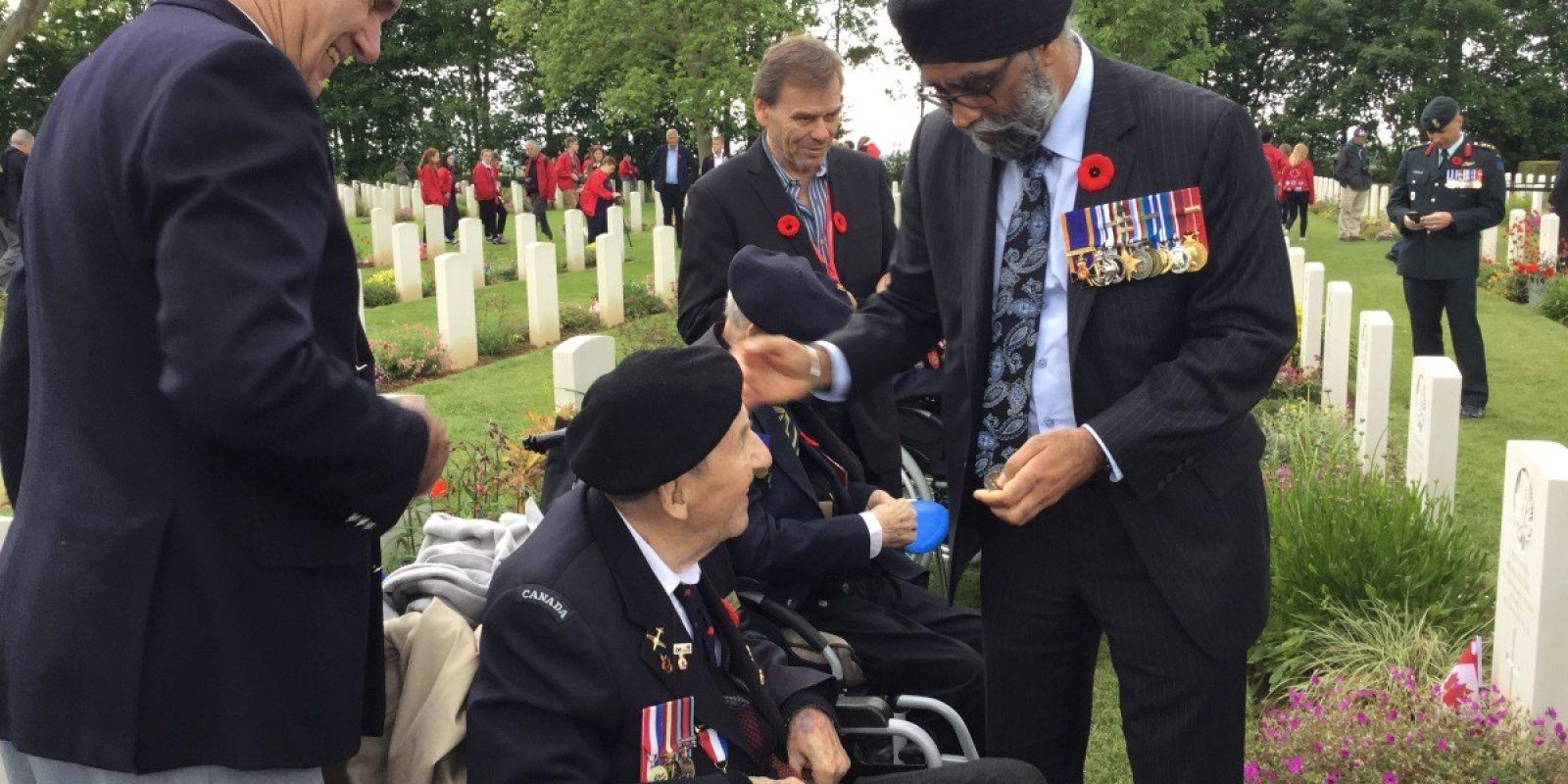 Sid Cole tijdens een D-Day plechtigheid in Normandië op 5 juni 2019, in gesprek met Harjit Sajjan, de Canadese minister van defensie. (Archief Sid Cole)