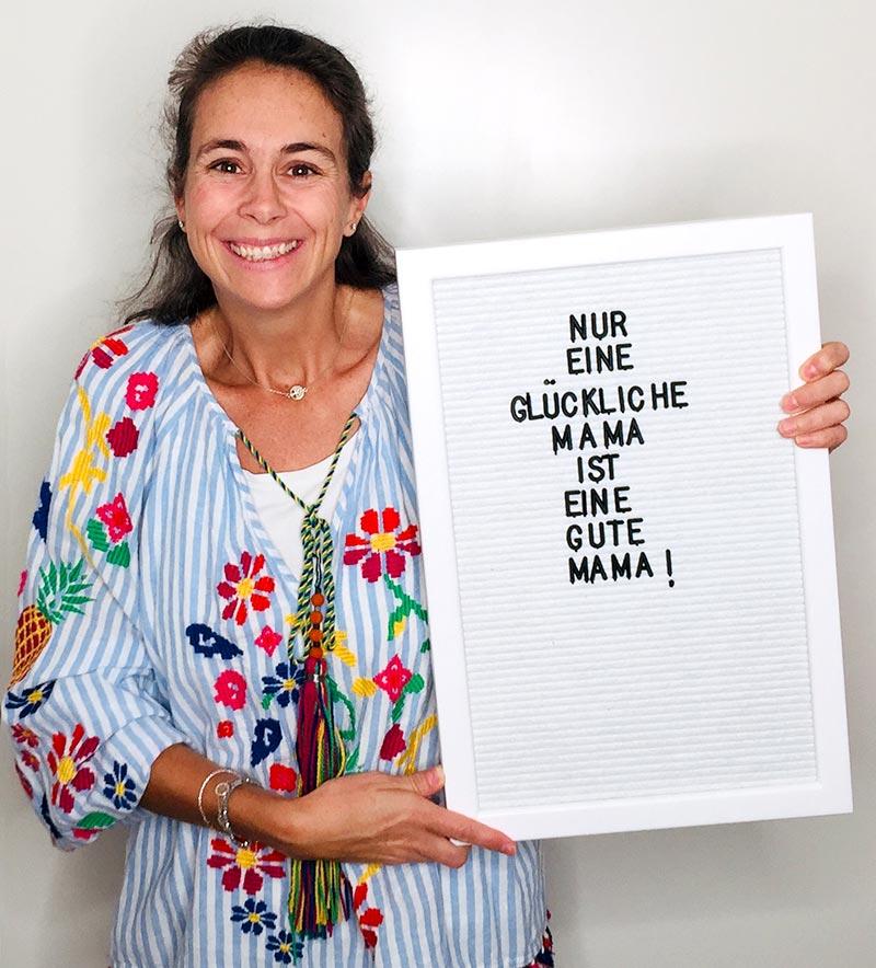 """Giulia hält ein Letterboard hoch: """"Nur eine glückliche Mama, ist eine gute Mama!"""""""