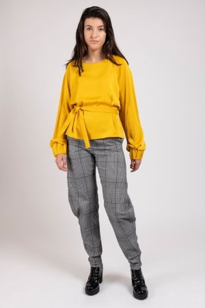 Model wearing yellow women's top with oversized sleeves and houndstooth curved trousers | Haruco-vert