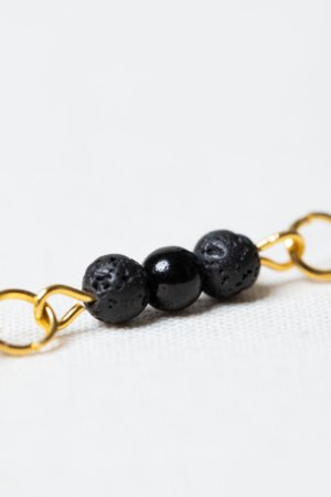 Golden earring set with lava stone and black glass beads