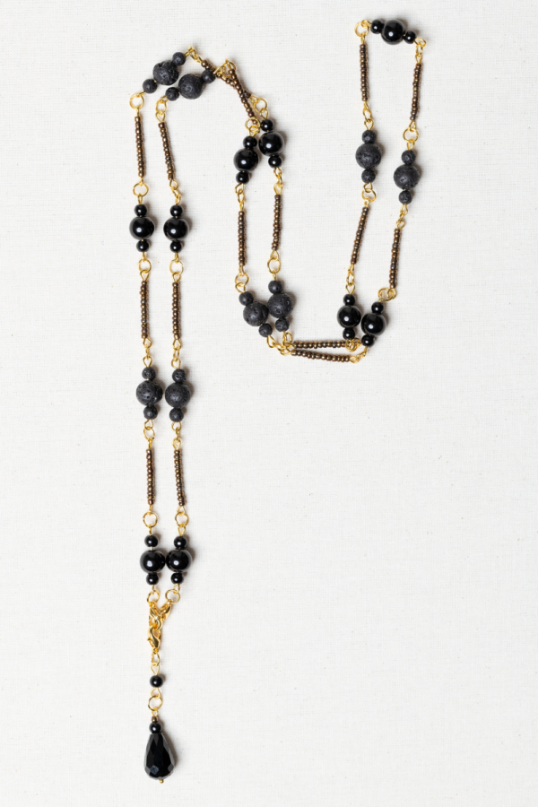 Long golden necklace with black beads and lava stones