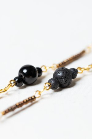 Long golden necklace with black and golden beads detail