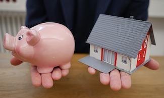 Haus und Sparschwein als Zeichen der Immobilienfinanzierung