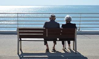 Mit der Leibrente zufriedenes Seniorenpaar auf einer Bank