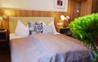 Ein helles Doppelzimmermit Bett