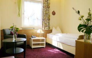 Ein helles Einzelzimmer, mit Sessel und 1 Bett