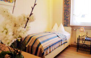 Ein helles Einzelzimmer und einem Bett