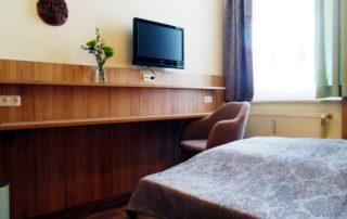 Ein helles Doppelzimmermit Bett und TV