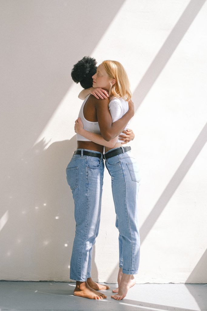 Two women dressed in light blue jeans and white tops embrace