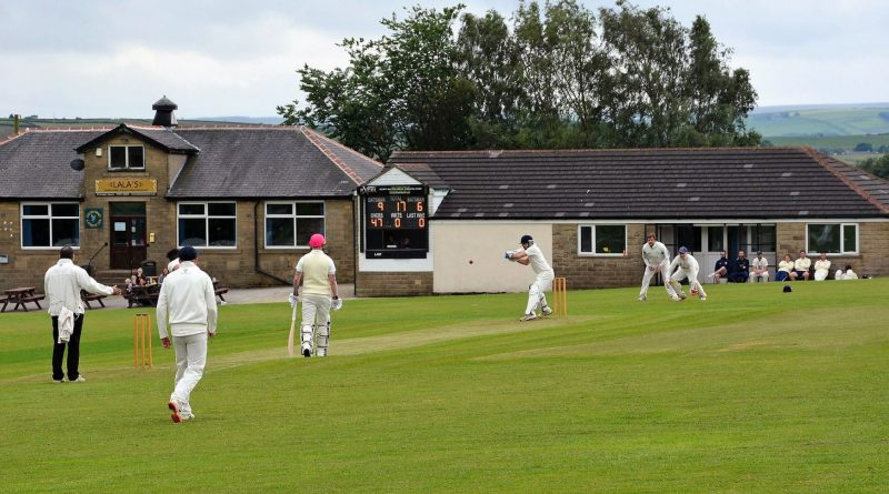Image shows Golcer cricket club, a 1-storey building with a cricket pitch in front where people are playing