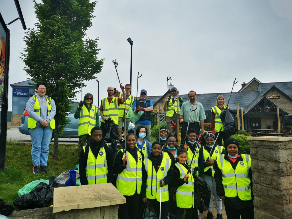 A group of around 20 people in high vis vests pose for a photograph with litter pickers held up