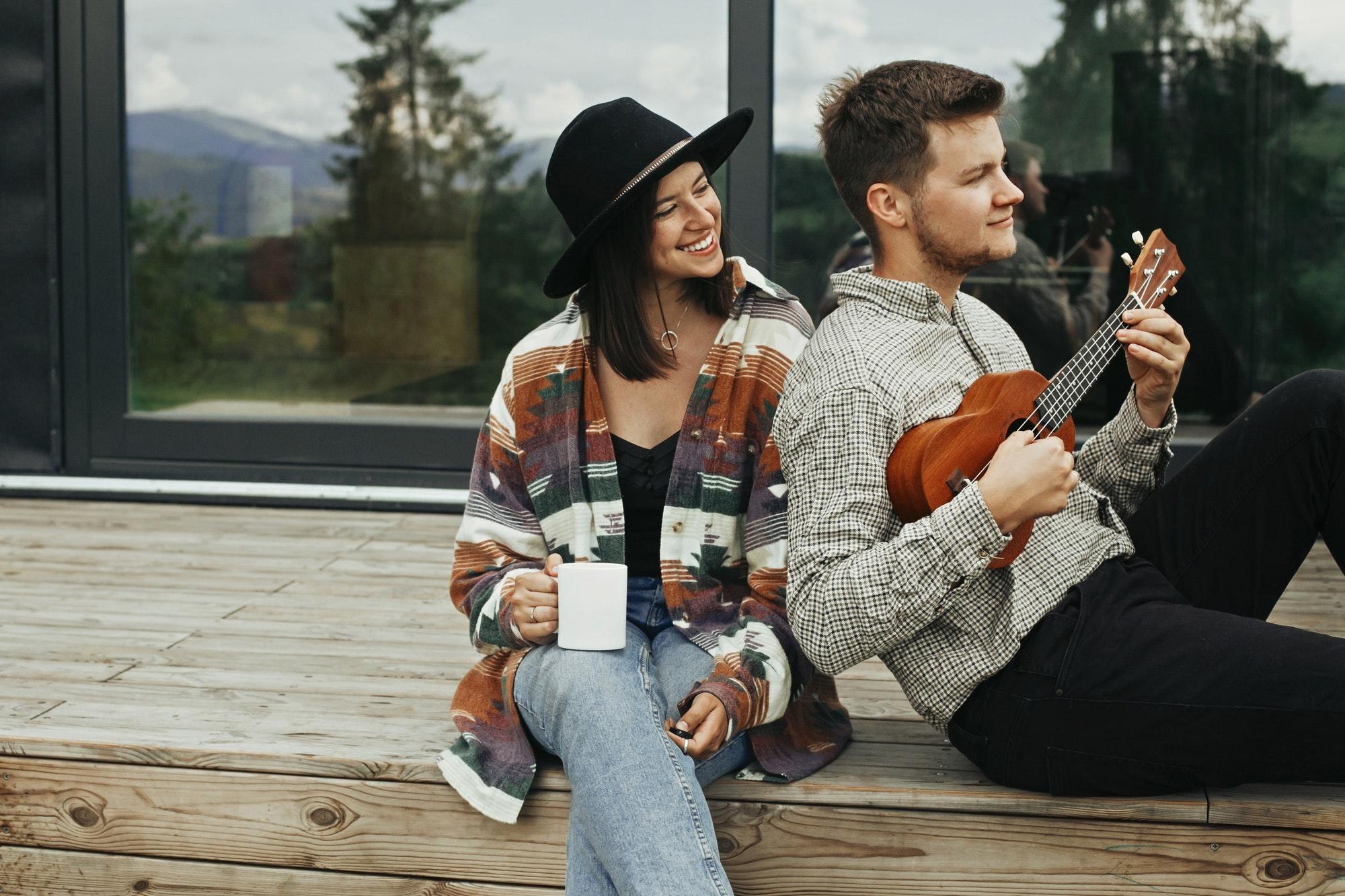 Hipster man playing on ukulele for his beautiful stylish woman