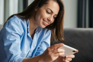 Image of woman playing video game on mobile phone while sitting