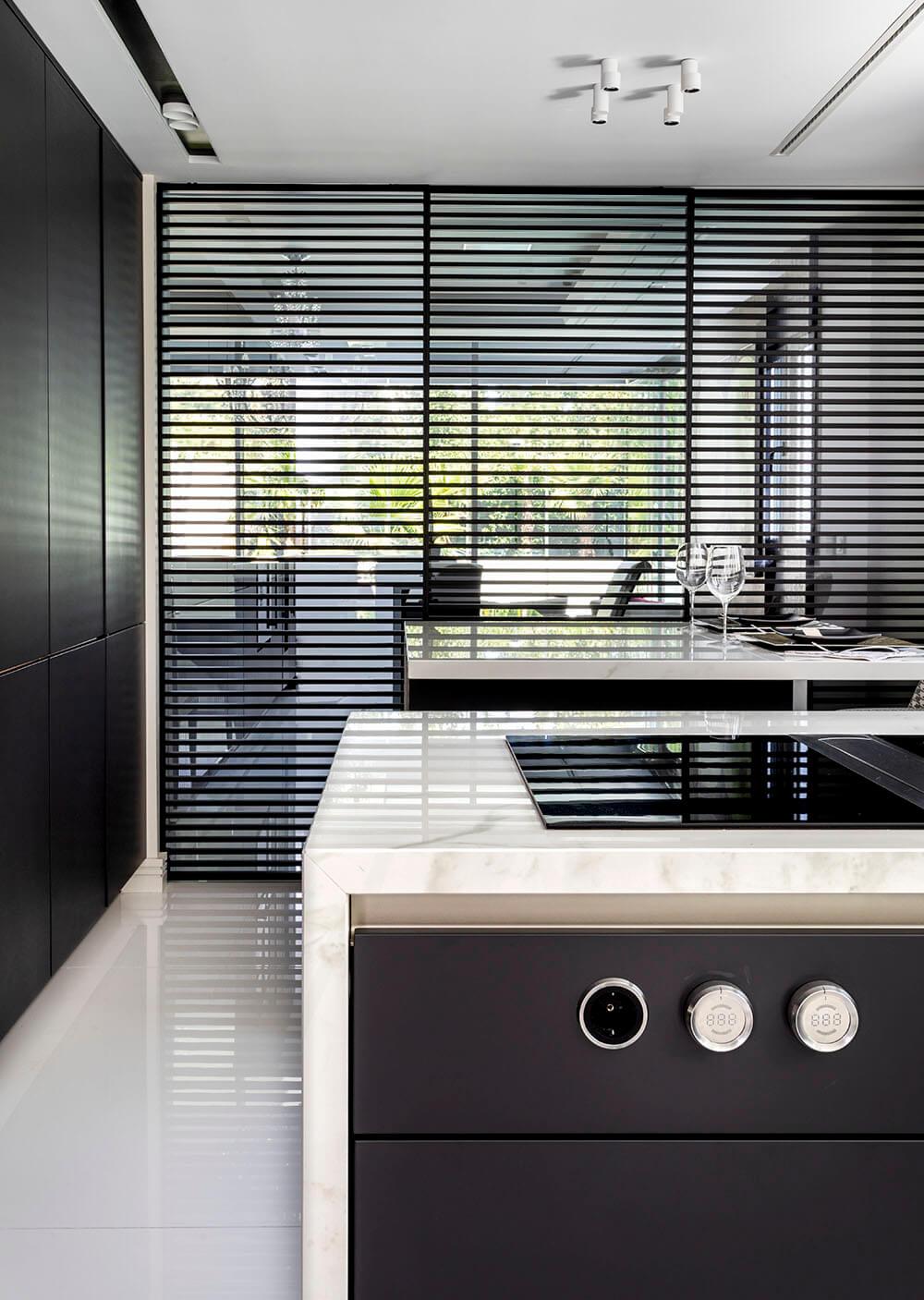 Cocina y salón integrado manteniendo a la vez la independencia mediante paneles móviles Stripe Rimadesio