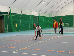 Photo of Blind tennis player playing tennis on indoor tennis court.