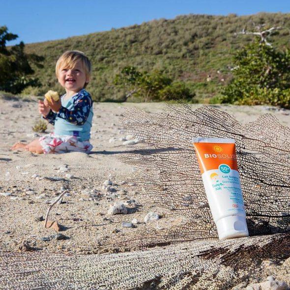 Viser tube med Sun Milk 50 og et lite barn på stranda