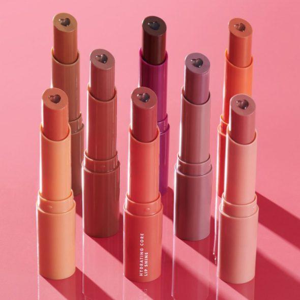 Viser 8 Hydration Core Lip Shine tuber fra elf, stående oppreist mot en mørk rosa bakgrunn