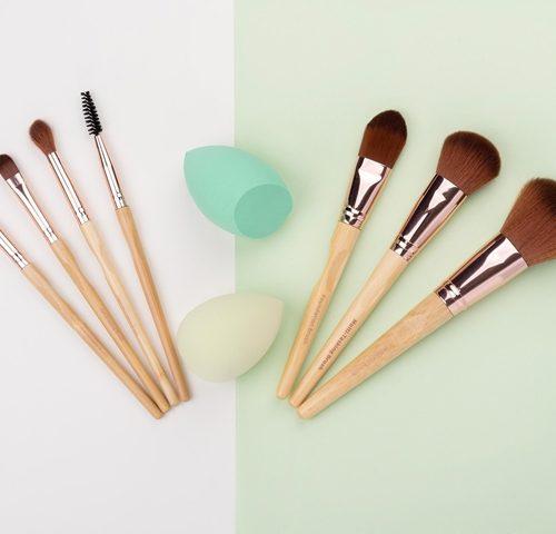 Viser alle 7 børstene og 2 svamper på en vertikal delt hvit og grønn bakgrunn. Fra The Ultimate Brush Collection settet fra So Eco