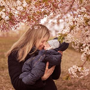 Mamma och baby fotograferade under blommande körsbärsträd i Nacka