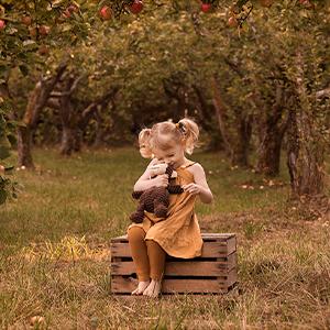 barn sitter på en träpall under äppelträden