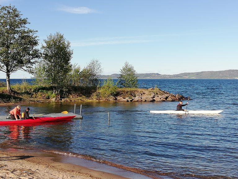 Bild på en kanotist på vattnet och en vid en brygga