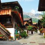 Wooden houses with flowers and mountains in Brienz