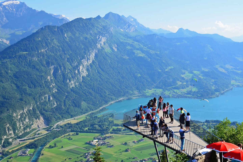 visitors enjoy the view from the Harder Kulm platform over Interlaken