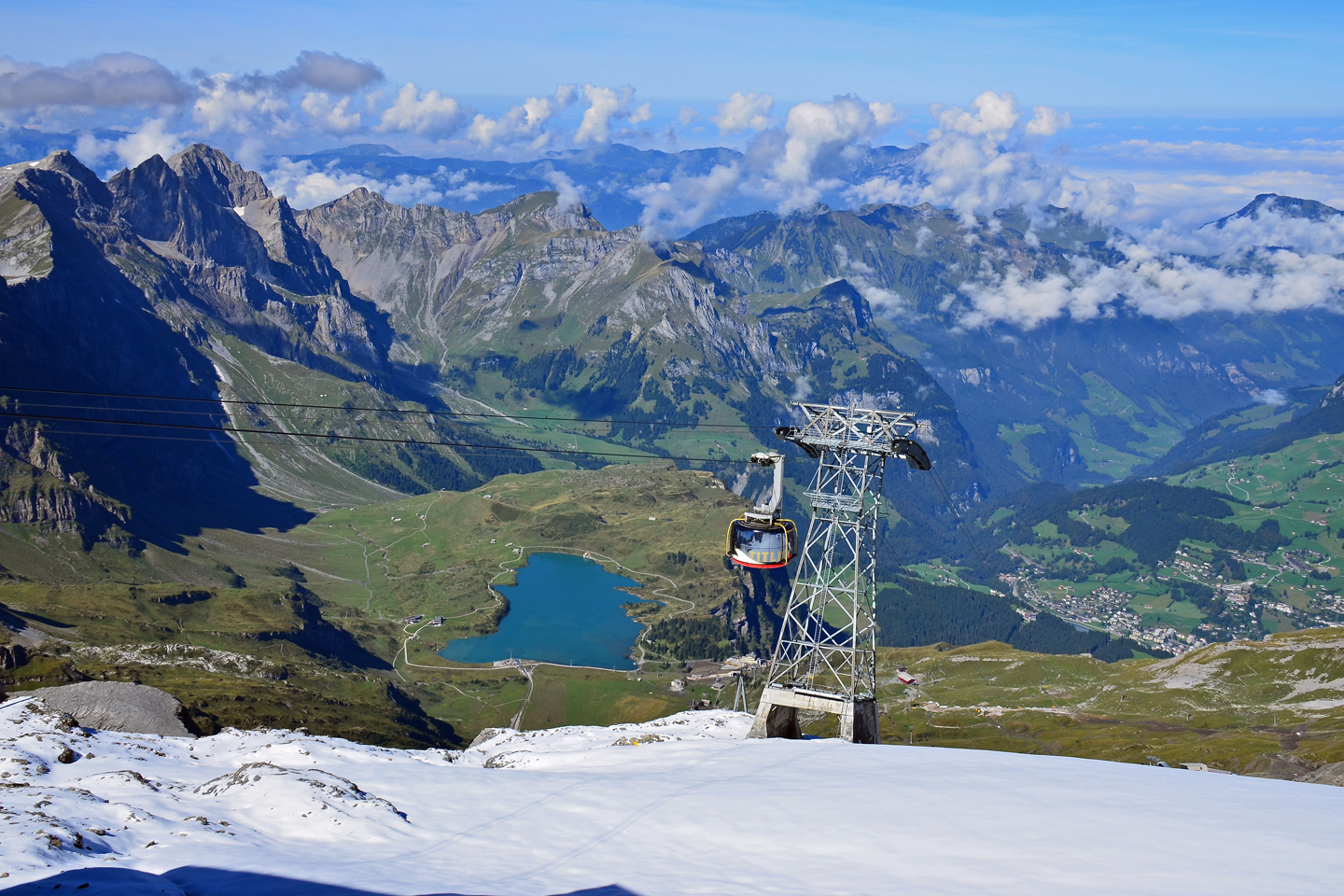 Titlis cable car over a mountain landscape with lake truebsee, one of the highlights of Switzerland