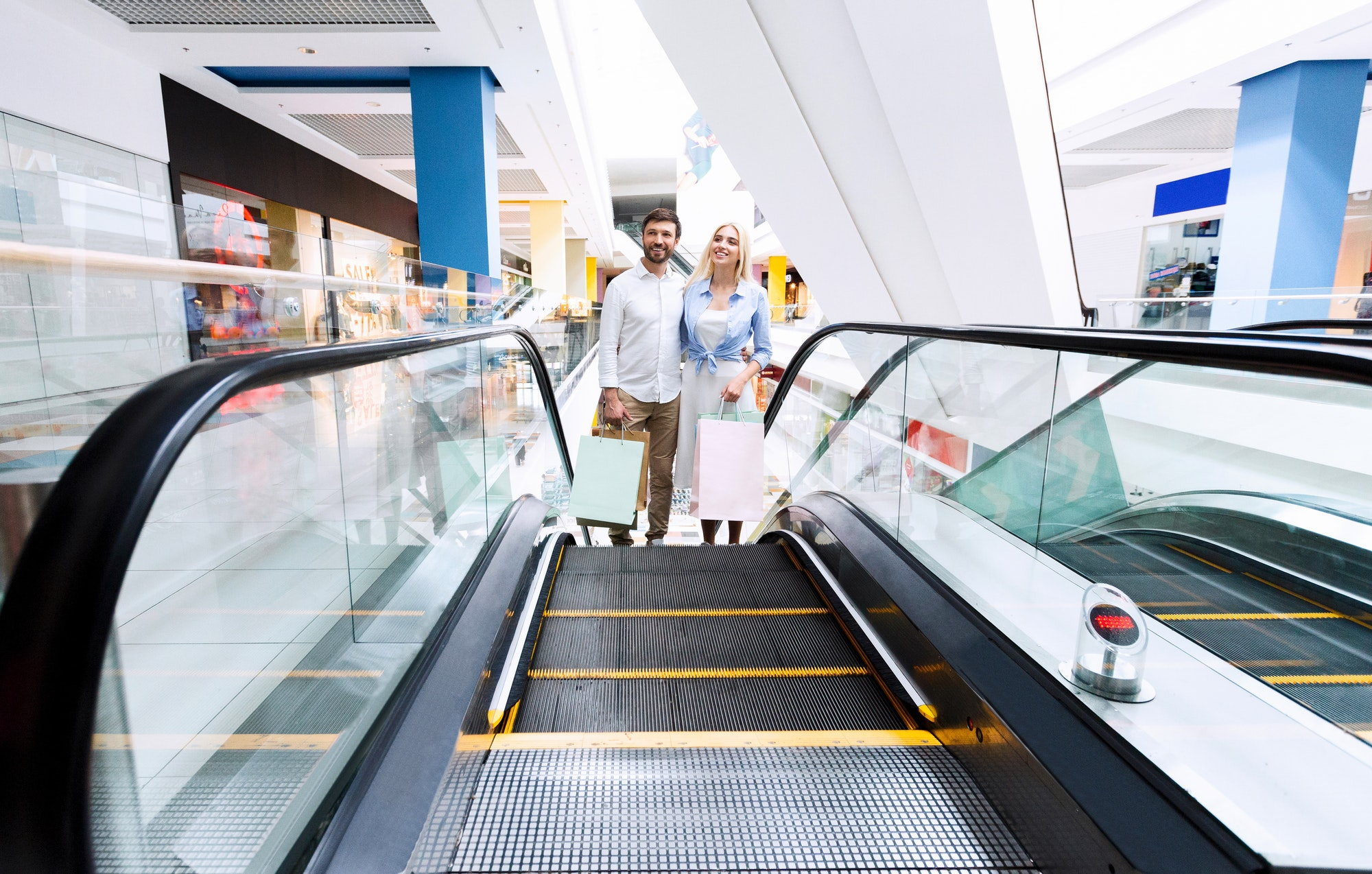 Couple Standing Hugging On Escalator Holding Shopping Bags In Mal