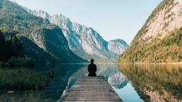 man zittend op pier aan berg meer als metafoor voor de visie