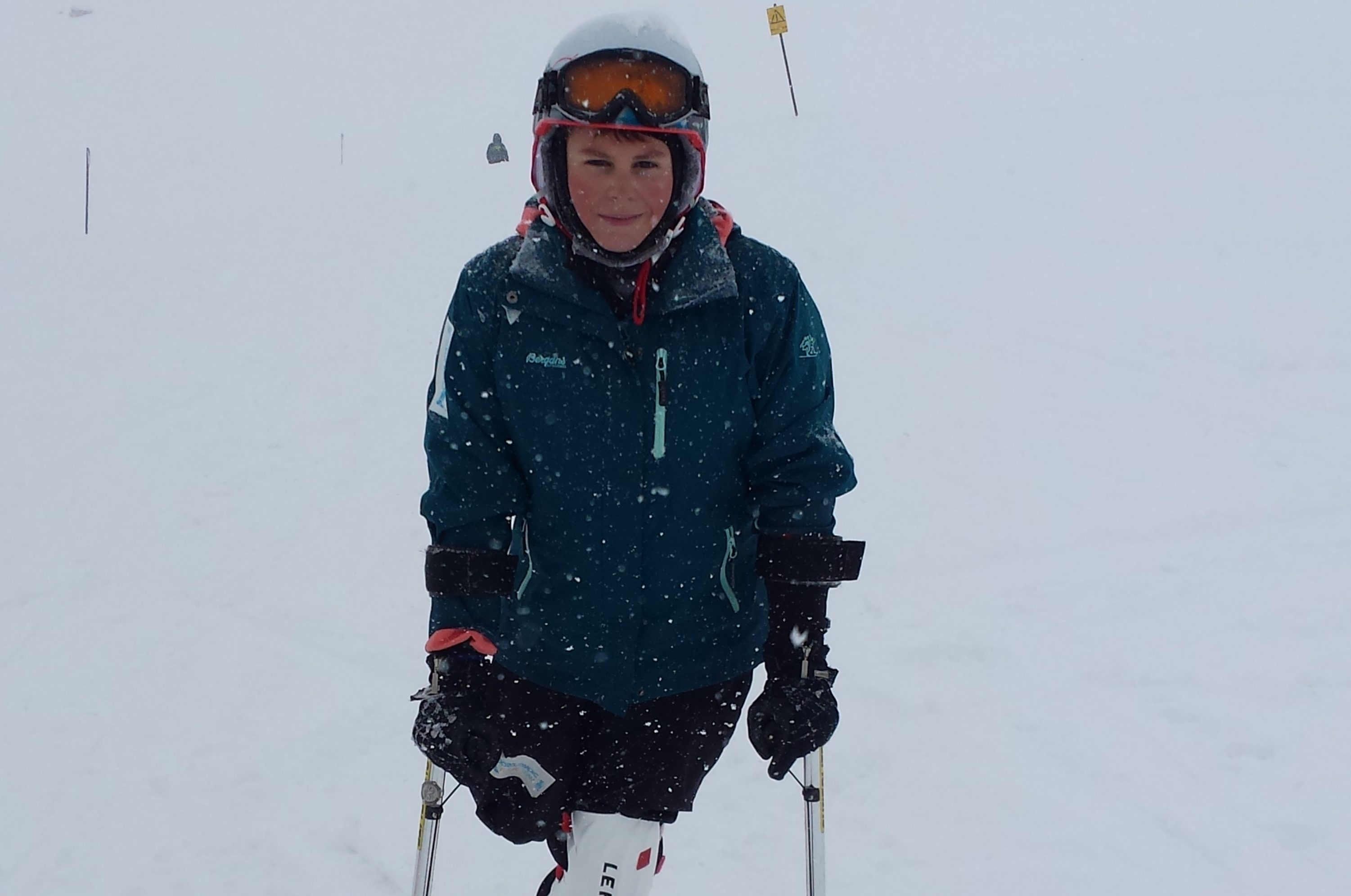 This picture shows a young boy standing on a skiing slope with a ski on his one remaining leg. Additionally, he has two supportive smaller skis on his arms. He has red cheeks, wears a helmet and smiles