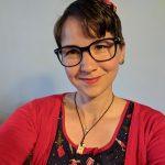 Karina trägt eine große schwarz-gerahmte Brille und eine rote Blume im braunen Haar. Außerdem ein 50er Jahre Kleid und eine rote Weste