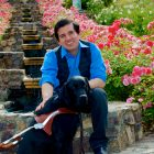 Belo Cipriani, a young man with black, short hair wears a blue shirt and black jeans and sits on stone steps in front of a sea of pink flowers. One hand lies on the back of his guide dog, a black labrador.