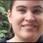 Caitlin Hernandez, eine junge Frau mit braunen, schulterlangen, glatten Haaren und braunen Augen lächelt.