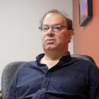 David-Elijah Nahmod, ein Mann mit Brille und kurzen, welligen, braunen Haaren sitzt in einem Bürostuhl und trägt ein blaues Hemd.