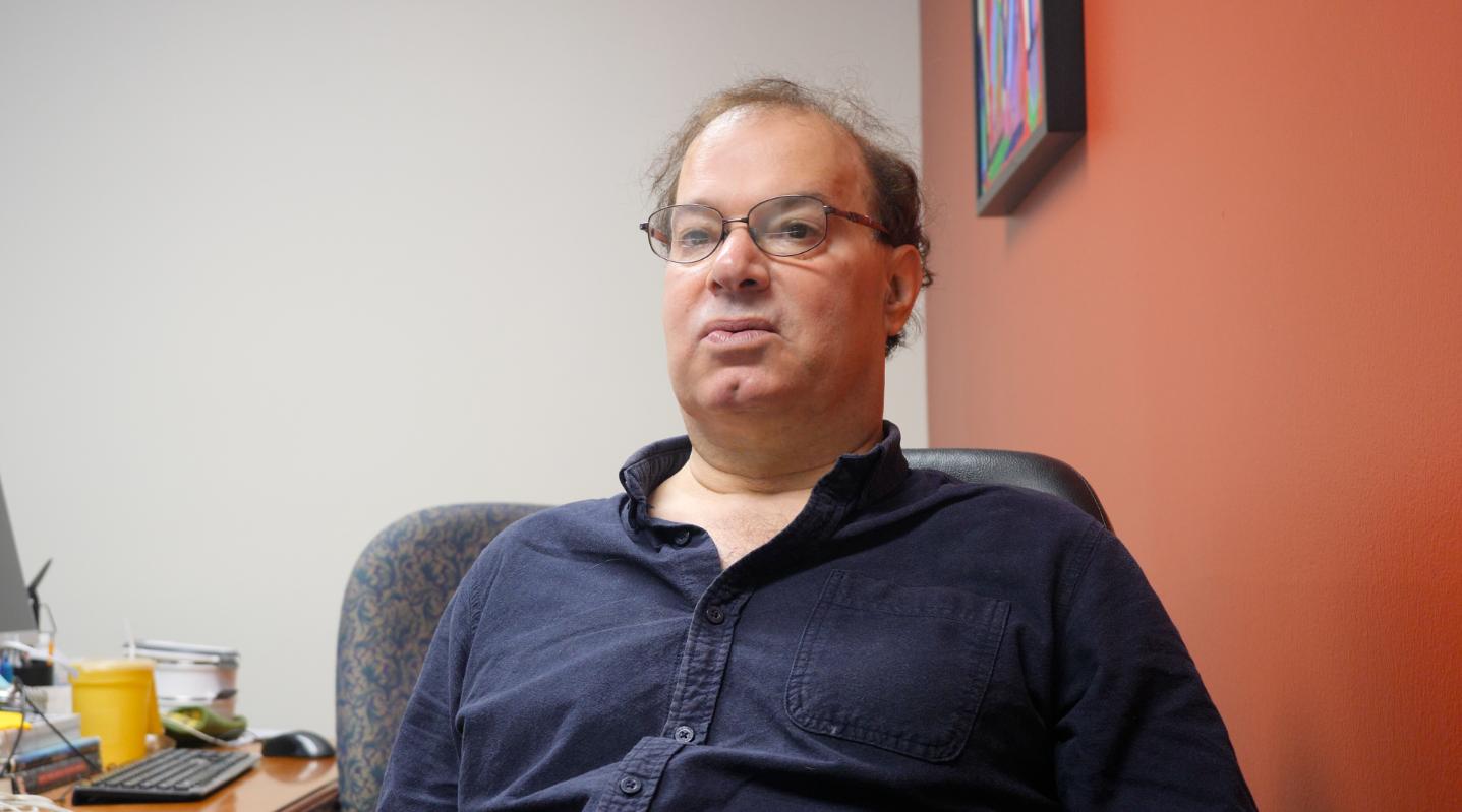 David-Elijah Nahmod, ein Mann mit Brille, braunen, welligen Haaren sitzt in einem Bürostuhl und trägt ein blaues Hemd.