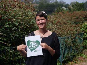 Karina hält ein Schild mit der Aufschrift: Yes, we care!