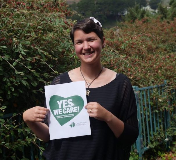 Karina is holding a sign saying: Yes, we care!