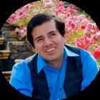 Belo Cipriani trägt ein blaues Hemd und lächelt. Er sitzt in einem auf einer Treppe vor blühenden roten Blumen