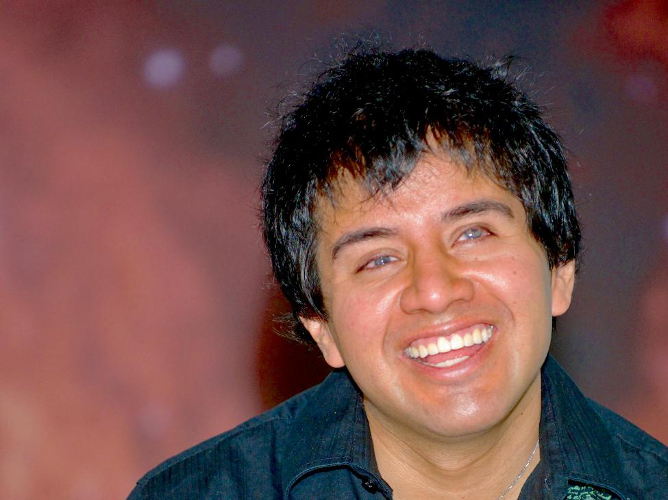 Belo Cipriani lächelt. Er hat schwarze, kurze Haare und trägt ein schwarzes Shirt
