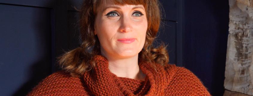 Frontalaufnahme einer Frau mit braunen Haaren, die auf beiden Seiten zu einem Zopf gebunden sind. Sie trägt einen warmen Wintersweater.