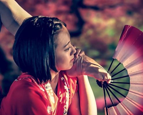 Eine Frau mit schulterlangen, schwarzen Haaren liegt auf dem Bauch. Ihre Füße streckt sie über den Rücken neben ihr Gesicht. Sie hält einen Fächer.