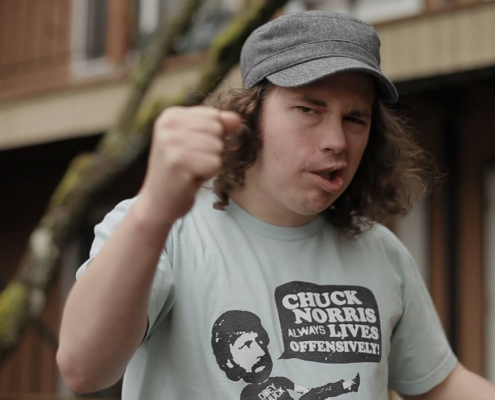 "Brandon stands outside his apartment with his fist in the air, making a serious face. His t-shirt has Chuck Norris, mid-kick. Chuck's speech bubble on the shirt says ""Chuck Norris Always Lives Offensively!"""